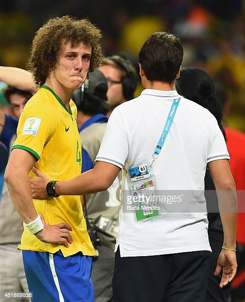 David Luiz of Brazil is consoled after a 71 defeat to Germany during the 2014 FIFA World Cup Brazil Semi Final match between Brazil and Germany at...