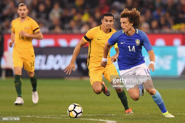 David Luiz of Brazil runs with the ball ahead of Tim Cahill of the Socceroos during the Brasil Global Tour match between Australian Socceroos and...