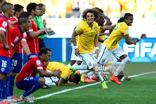 David Luiz of Brazil rushes to celebrate winning by a penalty shooting after the 2014 FIFA World Cup Brazil Round of 16 match between Brazil and...