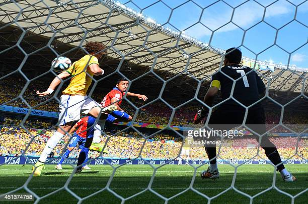 David Luiz of Brazil shoots and scores his team's first goal past goalkeeper Claudio Bravo of Chile hduring the 2014 FIFA World Cup Brazil round of...