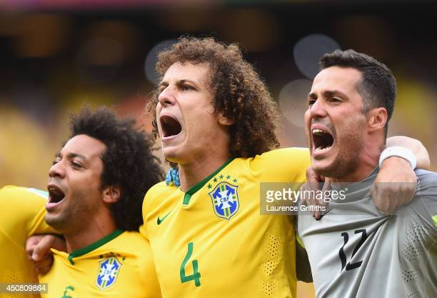 David Luiz of Brazil sings the National Anthem with Marcelo and Julio Cesar before the 2014 FIFA World Cup Brazil Group A match between Brazil and...