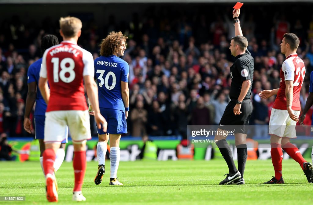 David Luiz of Chelsea is shown a red card by referee Michael Oliver during the Premier League match between Chelsea and Arsenal at Stamford Bridge on September 17, 2017 in London, England.