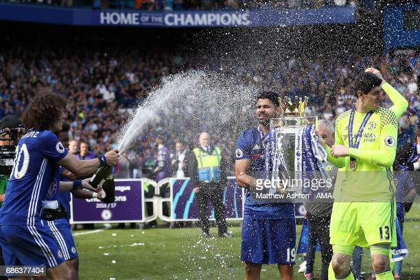 David Luiz of Chelsea sprays champagne as his teammates celebrate with the trophy at the end of the Premier League match between Chelsea and...