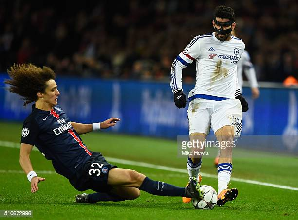 David Luiz of Paris SaintGermain slides to tackle Diego Costa of Chelsea during the UEFA Champions League round of 16 first leg match between Paris...