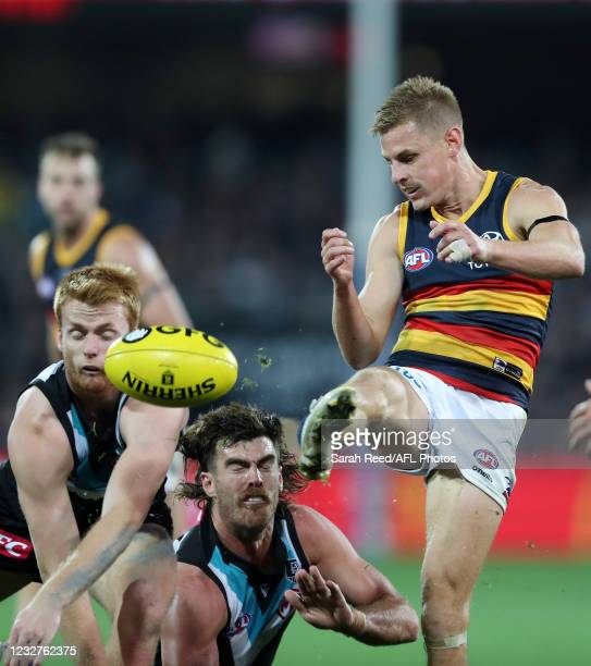 David Mackay of the Crows kicks the ball from Scott Lycett of the Power and Willem Drew of the Power during the 2021 AFL Round 08 match between the...