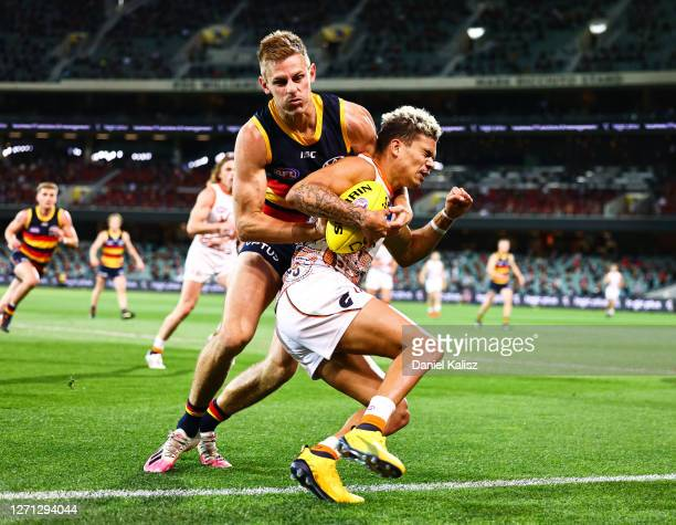 David Mackay of the Crows tackles Bobby Hill of the Giants during the round 16 AFL match between the Adelaide Crows and the Greater Western Sydney...