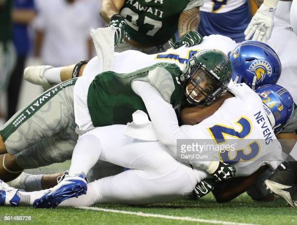 David Manoa of the Hawaii Rainbow Warriors takes down Tyler Nevens of the San Jose State Spartans during the first quarter of their game at Aloha...