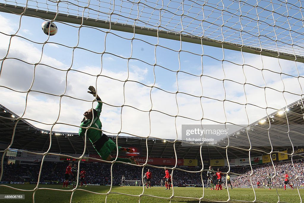 David Marshall the goalkeeper of Cardiff City dives in vain as the ball hits the crossbar from a shot by Jonathan Walters of Stoke City during the Barclays Premier League match between Cardiff City and Stoke City at the Cardiff City Stadium on April 19, 2014 in Cardiff, Wales.