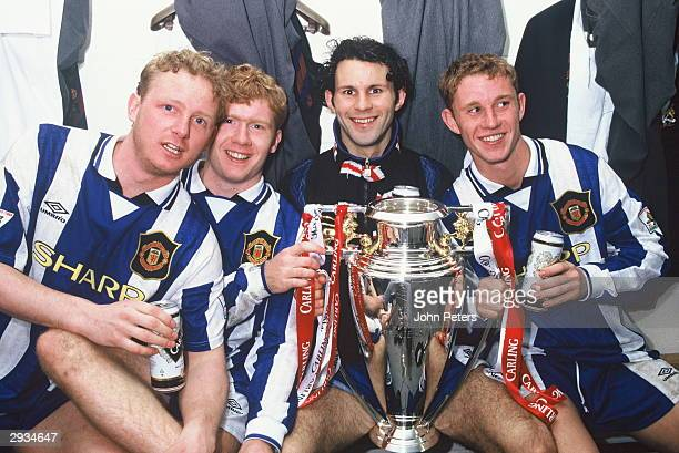 David May, Paul Scholes, Ryan Giggs and Nicky Butt of Manchester United celebrate in the dressing room with the FA Premiership Trophy after the...