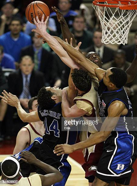 David McClure and Gerald Henderson of the Duke Blue Devils fight for the rebound with Joe Trapani and Rakim Sanders of the Boston College Eagles on...