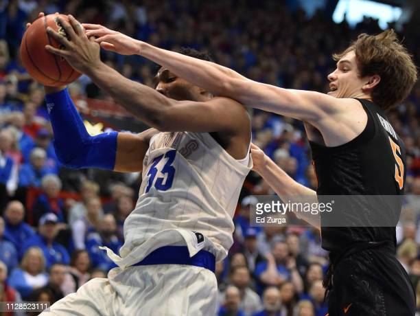 David McCormack of the Kansas Jayhawks rebounds the ball against Duncan Demuth of the Oklahoma State Cowboys in the first half at Allen Fieldhouse on...
