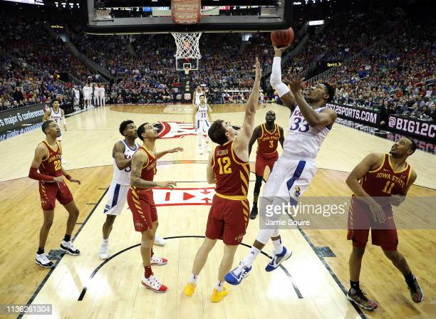 David McCormack of the Kansas Jayhawks shoots as Michael Jacobson of the Iowa State Cyclones defends during the Big 12 Basketball Tournament Finals...