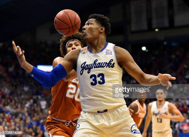 David McCormack of the Kansas Jayhawks tries to gain possession of the ball against Jericho Sims of the Texas Longhorns in the first half of a...