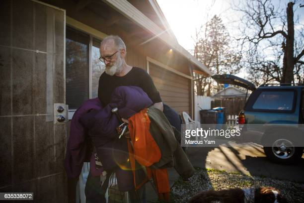 David McGlamery caries personal belongings back into their home along the Feather River in Oroville Calif on Feb 14 2017 The family had to retreat to...