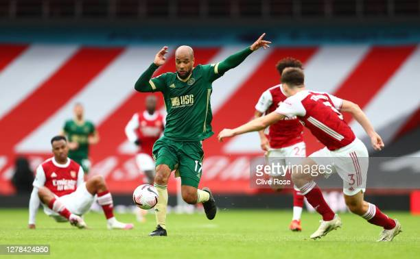 David McGoldrick of Sheffield United controls the ball as Kieran Tierney of Arsenal looks on during the Premier League match between Arsenal and...