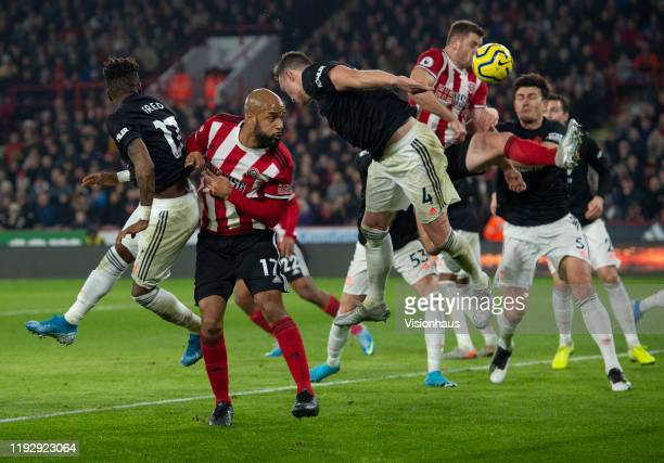 David McGoldrick of Sheffield United goes up for a header with Phil Jones and Fred of Manchester United during the Premier League match between...