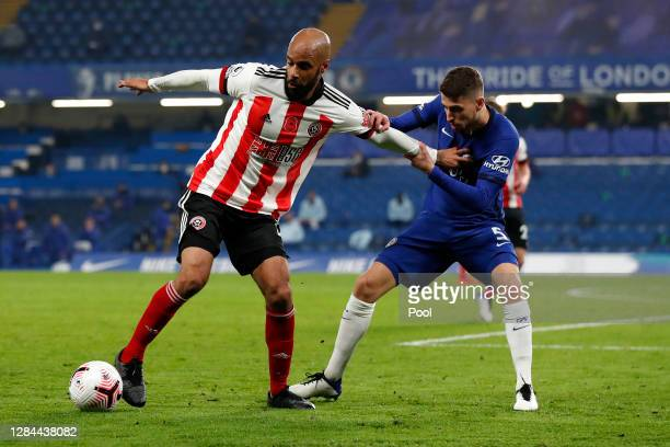 David McGoldrick of Sheffield United is challenged by Jorginho of Chelsea during the Premier League match between Chelsea and Sheffield United at...