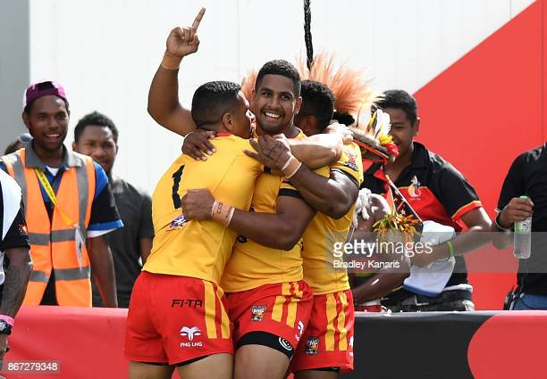 David Mead of Papua New Guinea is congratulated by team mates after scoring a try during the Rugby League World Cup match between Papua New Guinea...