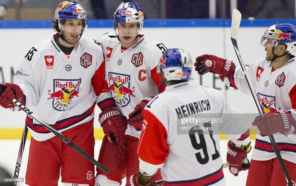 David Meckler #55 of Red Bull Salzburg celebrates his empty net goal with team mates Matthias Trattnig #51 and Dominique Heinrich #91 during the Champions Hockey League group stage game between HV71 Jonkoping and Red Bull Salzburg on August 24, 2014 in Jonkoping, Sweden.