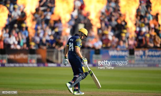 David Miller of Glamorgan checks the pitch as flares go off in the background during the NatWest T20 Blast match between Gloucestershire and...