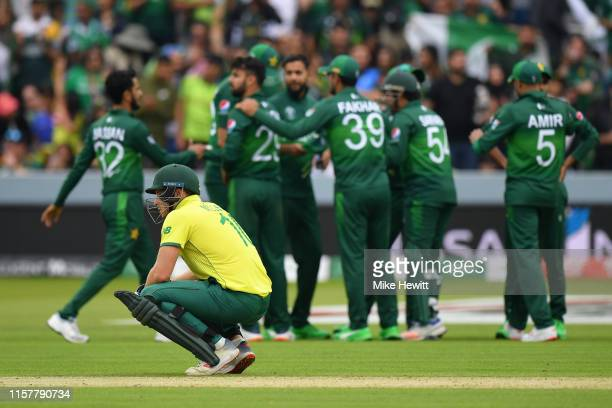 David Miller of South Africa is on his haunches as Pakistan players celebrate another wicket during the Group Stage match of the ICC Cricket World...