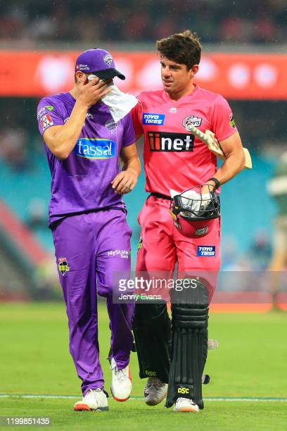 David Miller of the Hurricanes wipes his face as he walks off with Moises Henriques of the Sixers after rain stopped play during the Big Bash League...