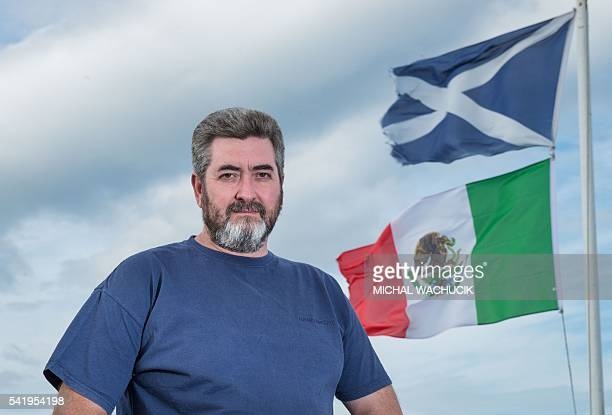 David Milne poses for a photograph beside the Mexican flag and The Saltire the flag of scotland on the top of his house located around 400 metres...