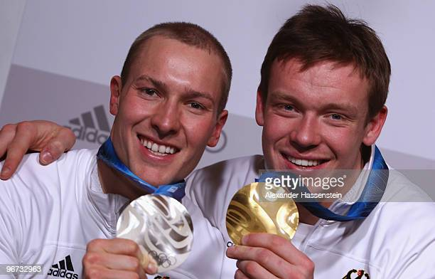 David Moeller of Germany celebrates with the silver medal and his teammate Felix Loch with his gold medal for their men's luge singles at the German...