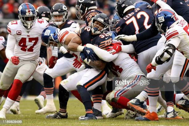 David Montgomery of the Chicago Bears runs with the ball while being tackled by Markus Golden of the New York Giants in the fourth quarter at Soldier...