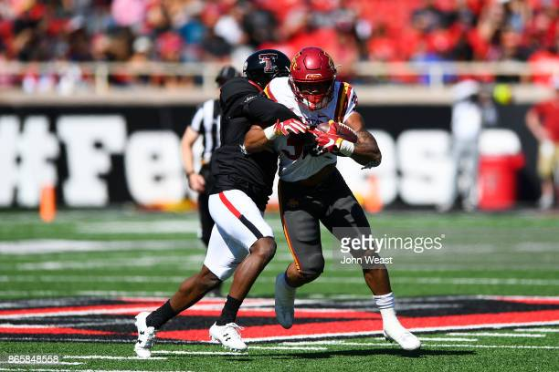 David Montgomery of the Iowa State Cyclones is wrapped up and tackled by Octavious Morgan of the Texas Tech Red Raiders during the game on October 21...