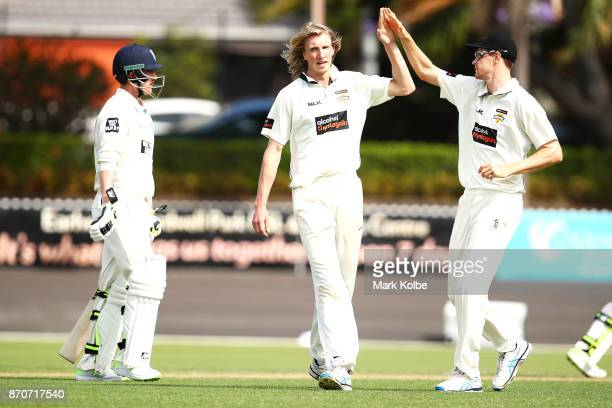 David Moody of the Warriors celebrates with Jason Behrendorff of the Warriors after taking the wicket of Nic Maddinson of the Blues during day three...