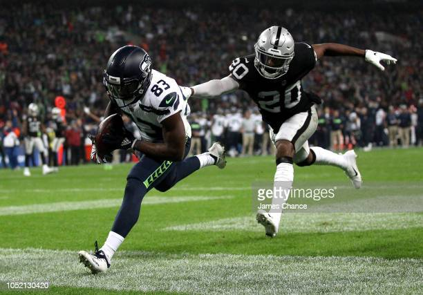 David Moore of Seattle Seahawks scores a touchdown as Daryl Worley of Oakland Raiders attemptst to tackle him during the NFL International series...