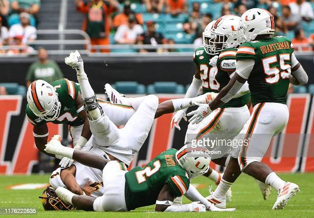 David Moore of the Central Michigan Chippewas is tackled by Al Blades Jr. #7 and Trajan Bandy of the Miami Hurricanes in the first half at Hard Rock...