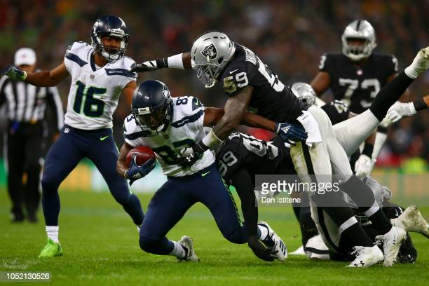 David Moore of the Seattle Seahawks is tackled by Arden Key of the Oakland Raiders and Tahir Whitehead of the Oakland Raiders during the NFL...