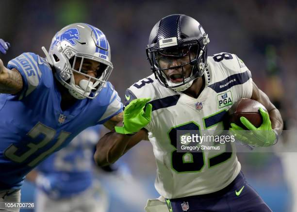 David Moore of the Seattle Seahawks runs for yardage against Teez Tabor of the Detroit Lions during the second half at Ford Field on October 28 2018...