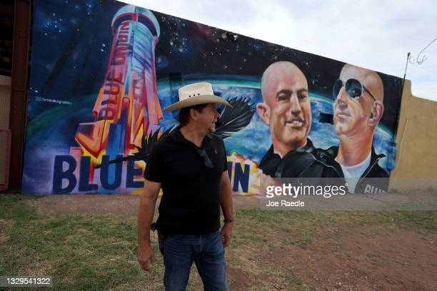 David Morales stands near a mural on the side of his building he had painted to honor Jeff Bezos as the billionaire plans to launch his Blue Origin...