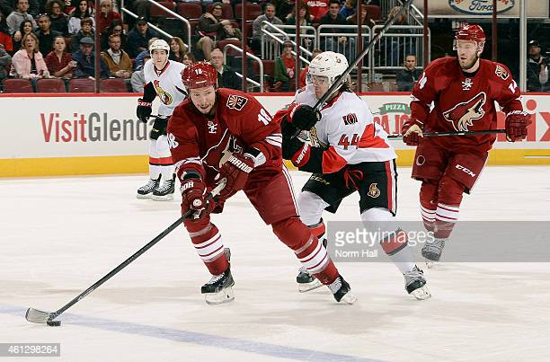 David Moss of the Arizona Coyotes skates with the puck ahead of JeanGabriel Pageau of the Ottawa Senators as Joe Vitale of the Coyotes trails the...