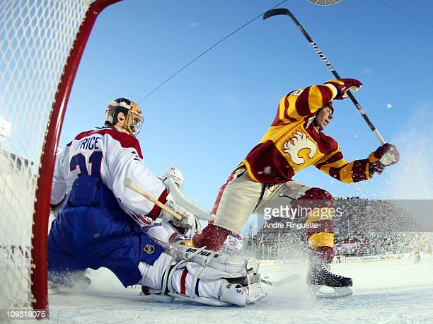 David Moss of the Calgary Flames bumps Carey Price of the Montreal Canadiens during the 2011 NHL Heritage Classic Game at McMahon Stadium on February...