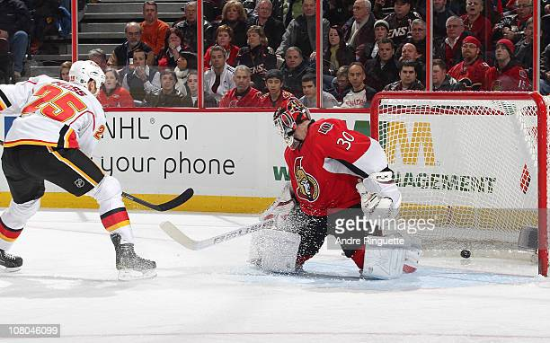 David Moss of the Calgary Flames slides the puck behind Brian Elliott of the Ottawa Senators for a second period goal at Scotiabank Place on January...