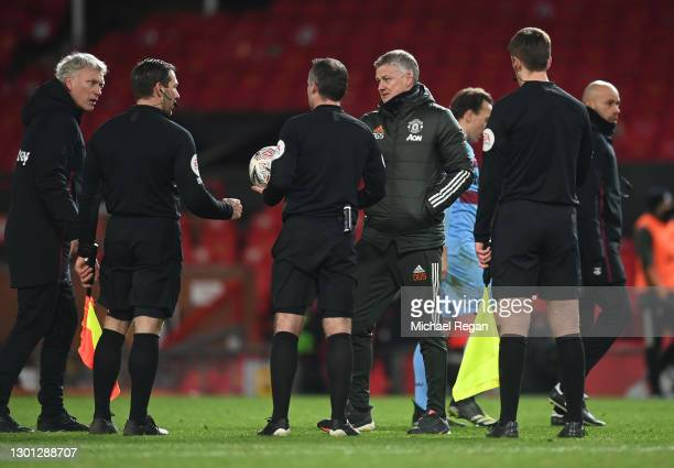 David Moyes, Manager of West Ham and Ole Gunnar Solskjaer, Manager of Manchester United talk to Match officials Paul Tierney, Constantine Hatzidakis...