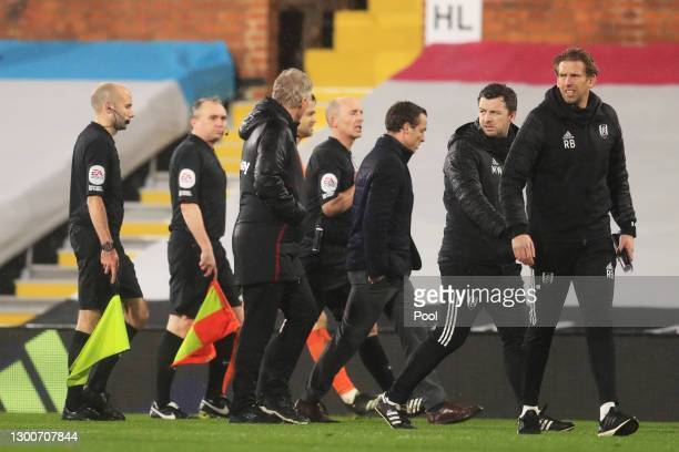 David Moyes, Manager of West Ham looks at match referee Mike Dean as they leave the field of play following the Premier League match between Fulham...