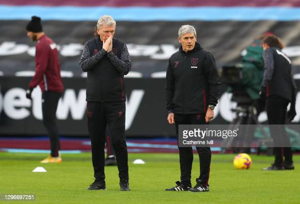 David Moyes, Manager of West Ham United talks with Alan Irvine, Assistant Manager of West Ham United during the warm up prior to during the Premier...