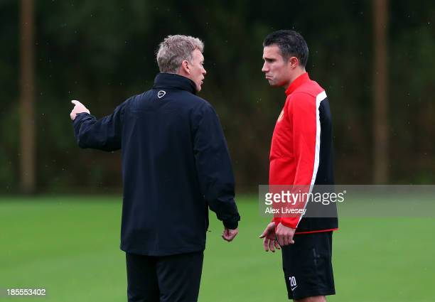 David Moyes the manager of Manchester United talks with Robin Van Persie prior to a training session at Aon Training Complex on October 22 2013 in...