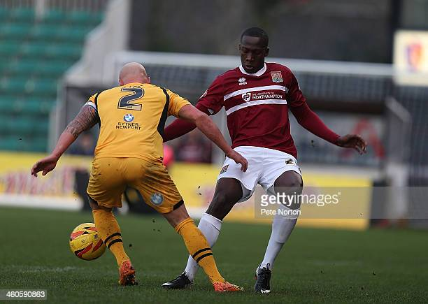 David Moyo of Northampton Town contests the ball with David Pipe of Newport County AFC during the Sky Bet League Two match between Newport County and...