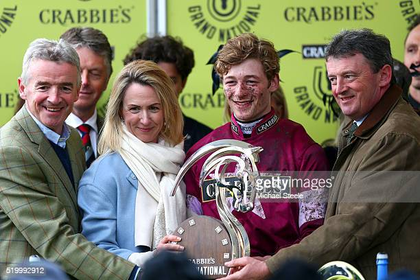 David Mullins poses with the winner's trophy next to owner Michael O'Leary and his wife Anita O'Leary in the Winners' Enclosure after riding Rule The...