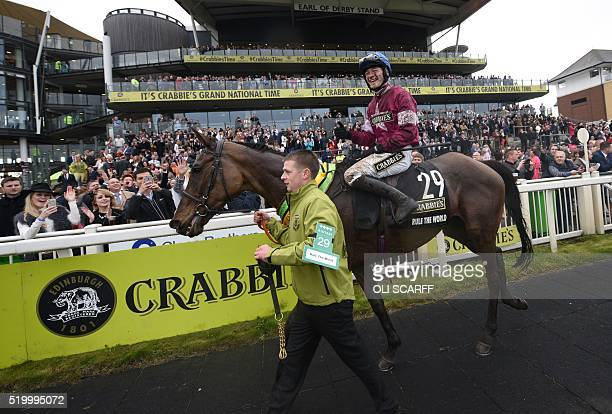 David Mullins riding 'Rule the World' is led from the field after winning The Grand National Steeple Chase on the final day of the Grand National...