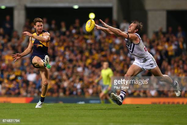 David Mundy of the Dockers attempts to smother the kick by Jack Redden of the Eagles during the round six AFL match between the West Coast Eagles and...
