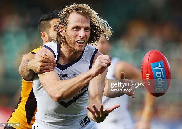 David Mundy of the Dockers handballs away from Paul Puopolo of the Hawks during the round eight AFL match between the Hawthorn Hawks and the...
