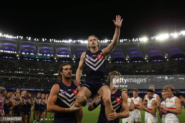 David Mundy of the Dockers is chaired from the ground by Alex Pearce and Nathan Fyfe after playing his 300th game during the round 6 AFL match...