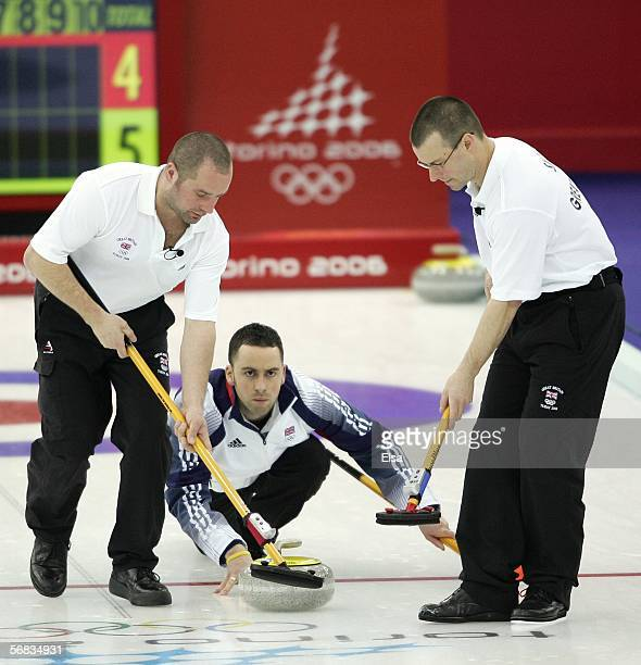 David Murdoch of Great Britain lines up a shot as Euan Byers and Warwick Smith sweep during the preliminary round of the men's curling between Great...